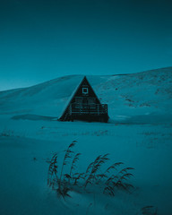 Wooden A frame house in blue light on snowy landscape