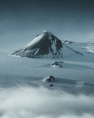 Large black hill in the center of a flat snowy landscape