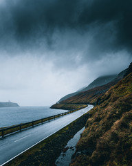Dark clouds over an empty coastal road in the Faroe Islands