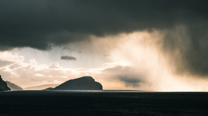 Rain clouds in the distance followed by sunlight  in the Faroe Islands