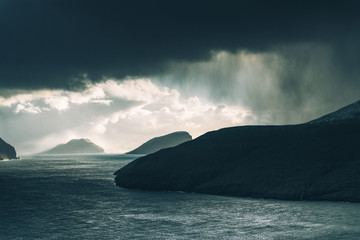 Rain falling from distant clouds over water in the Faroe Islands