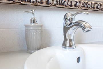 Soap and shampoo dispensers on Water tap sink with faucet in expensive loft bathroom