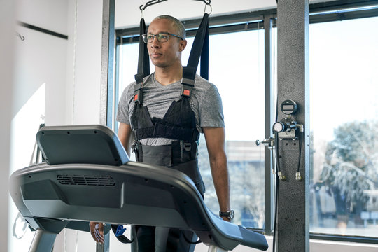 Man in physical therapy harness on a treadmill