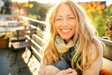 Portrait of happy blond mature woman on balcony in autumn