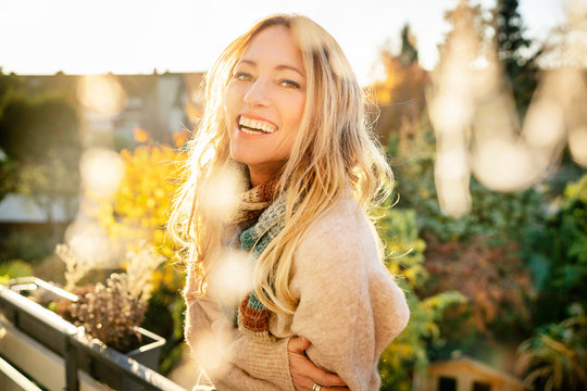 Portrait of laughing blond mature woman on balcony at autumn
