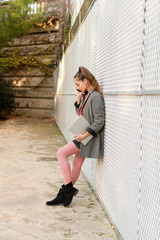 Young woman leaning on a wall, talking on the phone, holding digitaˆ tablet