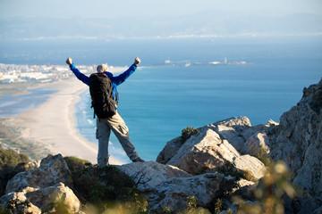 Spain, Andalusia, Tarifa, man on a hiking trip at the coast looking at view cheering