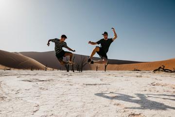 Namibia, Namib desert, Namib-Naukluft National Park, Sossusvlei, two men jumping in Deadvlei