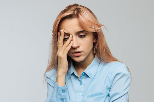 Displeased woman nearly falling asleep at work, hold her head with hand.Sleepy student spending time in university, feels lack of energy. Sleep deprivation, insomnia, apathy, weariness concept