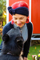 Portrait of smiling senior woman with red dyed hair face to face with her dog in the garden