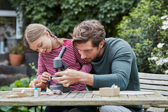 Father and daughter using microscope together at garden table