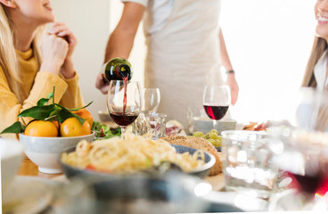 Friends having lunch together, host pouring red wine