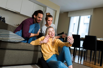 Friends sitting on couch in livingroom, using smartphone, chatting
