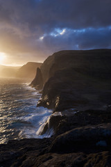 Vertical picture of colorful sunset over the wild rocky coastline and storm atlantic ocean in Faroe island Vagar during spring evening. Faroe islands, wild scandinavian landscape of rocks and cliffs.