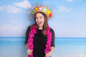 Fun photo booth props and young women on a oceanic scene background wearing an Hawaiian straw hat