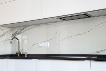 White glossy kitchen with black quartz countertop and marble tile backsplash. Build-in hidden incorporated hood and undermounted sink.