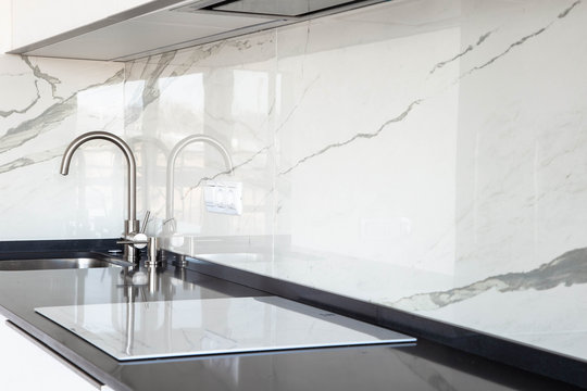 Close up of white glossy kitchen with black quartz countertop and marble tile backsplash. Build-in hidden incorporated hood and undermounted sink.