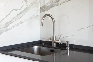 Close up of a undermounted sink and mixer in white and black kitchen design with marble tile backsplash and dark grey quartz countertop.