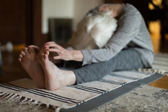 Elderly woman stretching on floor