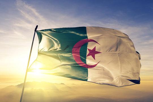 Algeria flag waving on the top sunrise mist fog