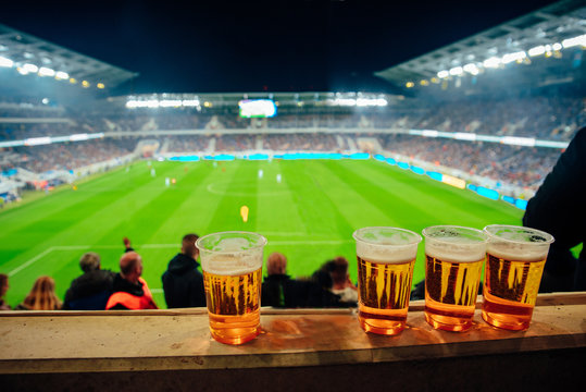 Beers at soccer stadium. Football game in background