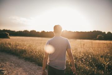 Mann wandert durch ein Feld im Sommer im Gegenlicht Fotoväggar