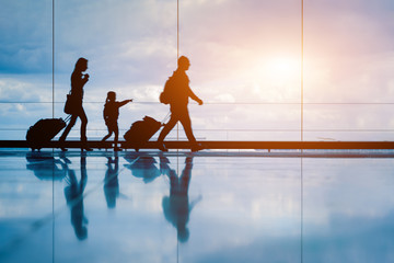Family at airport travelling with young child and luggage walking to departure gate, girl pointing at airplanes through window, silhouette of people, abstract international air travel concept Fotomurales