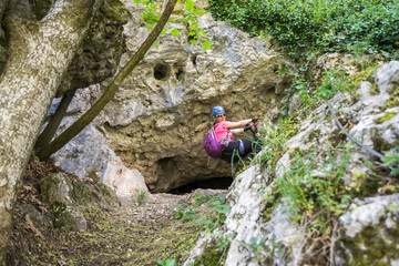 "Strong young woman near a cave entrance, during a via ferrata route called ""Amfiteatrul Zmeilor"" in Baia de Fier, Gorj county, Romania. Female tourist equipped with helmet, harness, klettersteig kit."