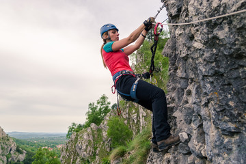 Young woman hanging from a via ferrata cable, while passing a difficult section, equipped with helmet, harness, kit. Klettersteig route at Baia de Fier, Pestera Muierilor, Romania, Gorj county.