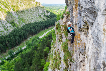 Female climber switching carabiners on a via ferrata route, vertical wall high above the valley, with a road behind. Klettersteig route at Baia de Fier, Pestera Muierilor, Romania, Gorj county.