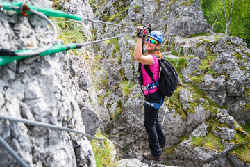 Happy young girl crossing a via ferrata wire bridge in Baia de Fier, Romania. Indian bridge on a klettersteig with a joyful, adventurous woman stepping across it.
