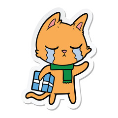 sticker of a crying cartoon cat holding christmas present