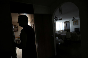 A local chats with a neighbour inside his flat during a blackout in Caracas