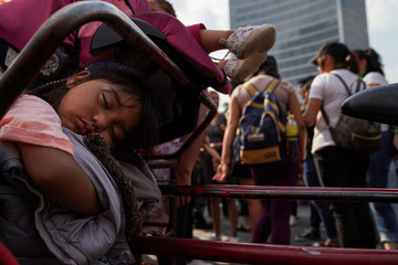 A girl sleeps during a march on International Women's Day in Mexico City