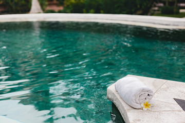 Towel and flower in luxury spa jacuzzi pool