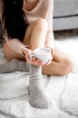 Woman in a cozy room with a cup of cocoa in her hand.