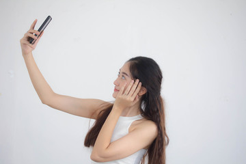 Portrait of thai china adult beautiful girl White shirt blue jeans using her smart phone Selfie