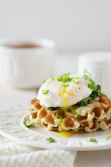 Waffles with poached egg and flowing yolk, cheese and spinach.