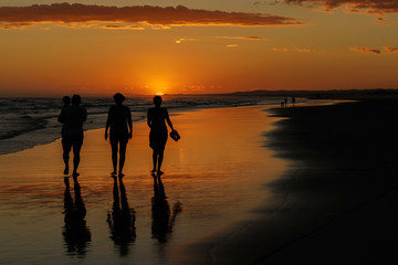 Silhouetted family walking on Birubi Beach, Port Stephens, NSW at sunset