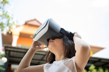 children wearing virtual reality glasses with fun and surprising face standing  outdoor
