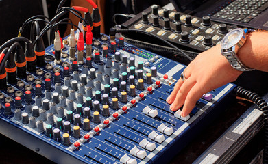 Professional mixing console with faders and adjusting knobs. The hand adjusts the sound.