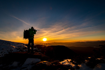 Red sunset and the silhoute of  photographer enthusiast stay on cliff and thinking..