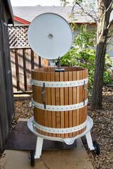 wine press in a back yard ready to press wine from crushed grapes