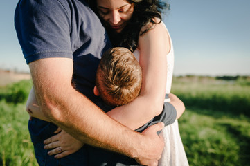 The son hugging parents on nature. Mom, dad and boy walk in the grass. Happy young family spending time together, outside, on vacation, outdoors. The concept of family holiday.