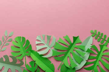 Pink background with green leaves of paper, minimalism