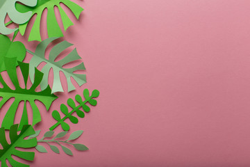 Pink background with green leaves of paper on the left side, minimalism
