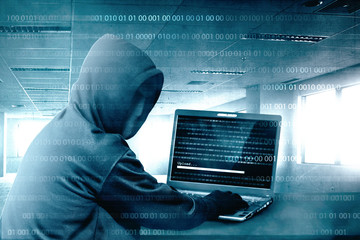 Hacker in black hoodie using laptop on the desk to hacking system with binary code and upload the malware