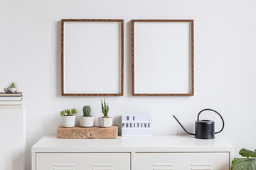 Minimalistic home decor of interior with two brown wooden mock up photo frames , white shelf with books, black watering can, cacti composition, box and home accessories. White walls. Mockup concept.