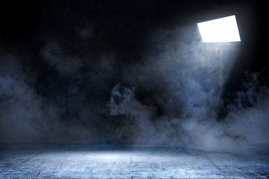 Room with concrete floor and smoke with light from spotlights
