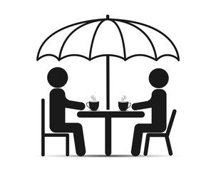 Two people sit at a table under an umbrella and drink tea or coffee